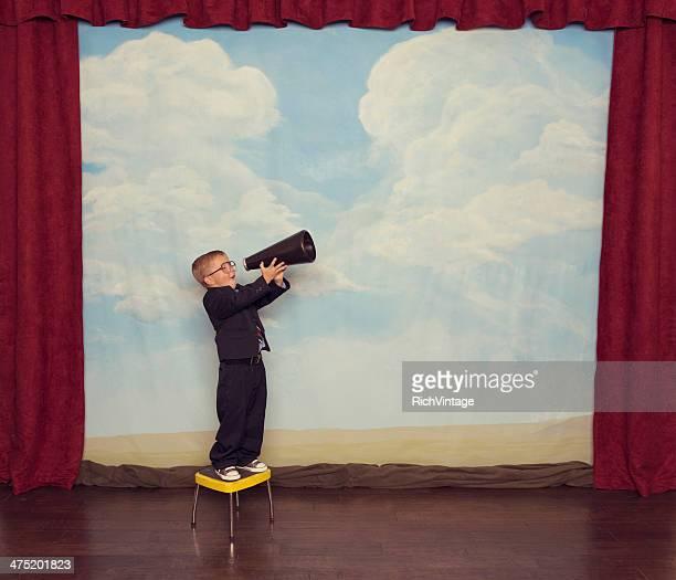 Junge Verkäufer brüllt mit Megafon auf der Bühne