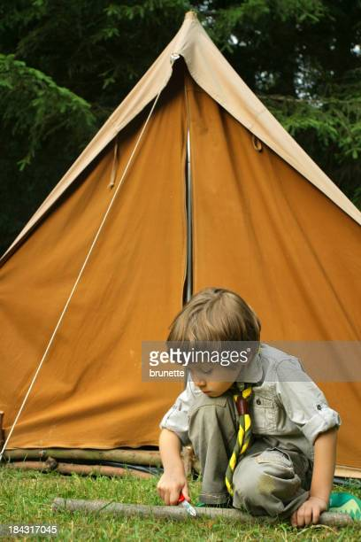 Young Boy Scout carving wood in front of a tent