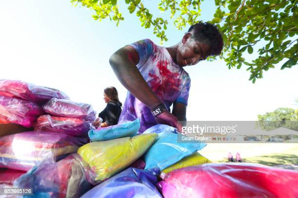 A young boy selects colorful abeer powder to spray on people to commemorate Holi and the arrival of the season of Spring as part of the annual...
