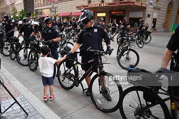 A young boy shakes a police officer's hand near the sight of the Republican National Convention in downtown Cleveland on the second day of the...