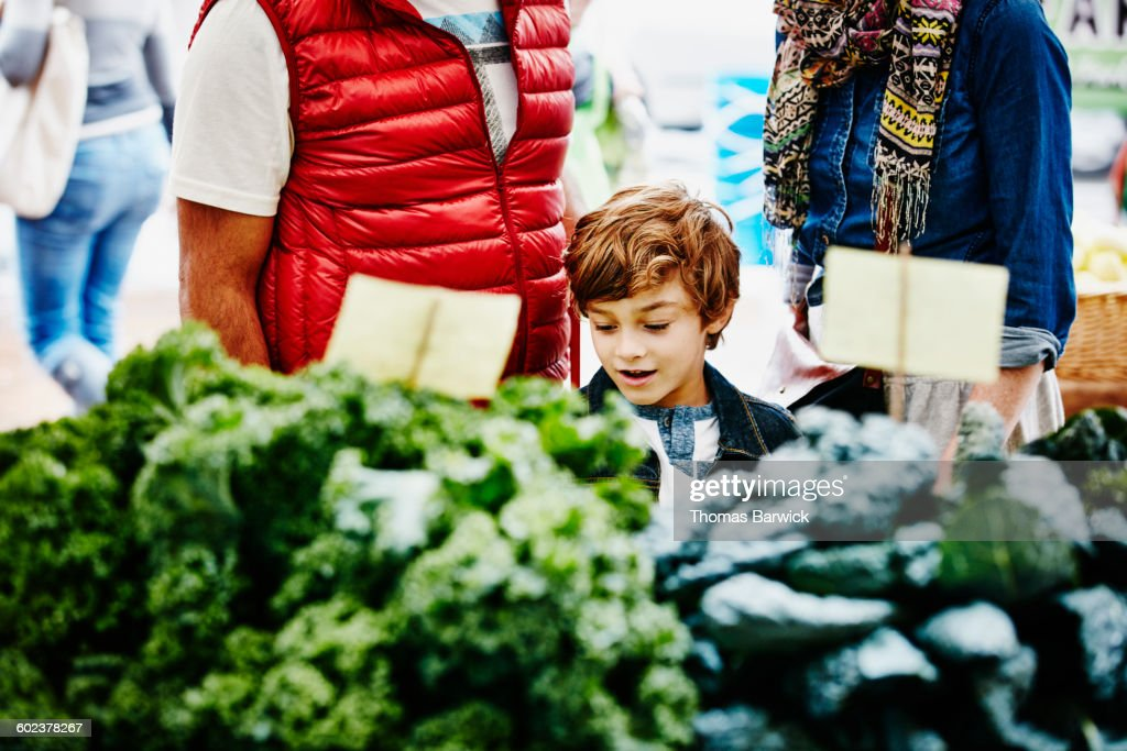 Young boy shopping at farmers market with parents