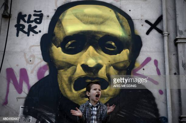 A young boy shouts in front of a street painting as he attends a military parade in central Athens during a ceremony marking the Greek Independence...