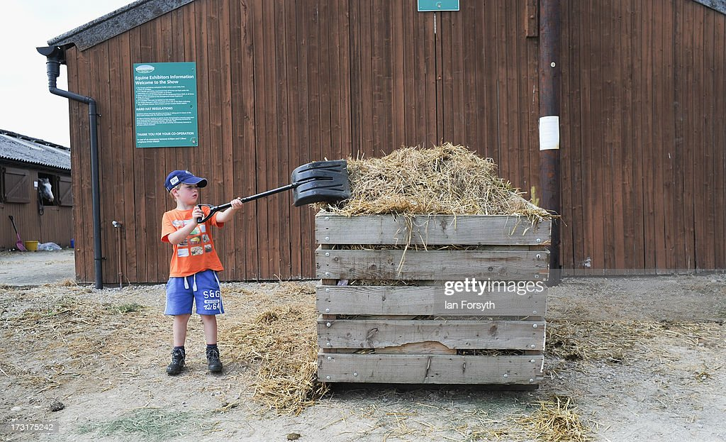 A young boy shovels hay into a storage container at the Great Yorkshire Show on July 9, 2013 in Harrogate, England. The Great Yorkshire Show is the UK's premier agricultural event and brings together agricultural displays, livestock events, farming demonstrations, food, dairy and produce stands as well as equestrian events to thousands of visitors over the three days.