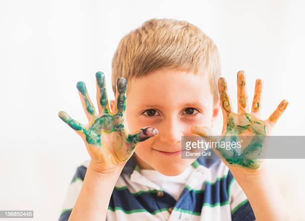 Young boy (6-7) showing hands stained with paint