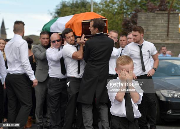 A young boy shows emotion as he covers his face while the funeral takes place of former IRA member Kevin McGuigan Sr on August 18 2015 in Belfast...