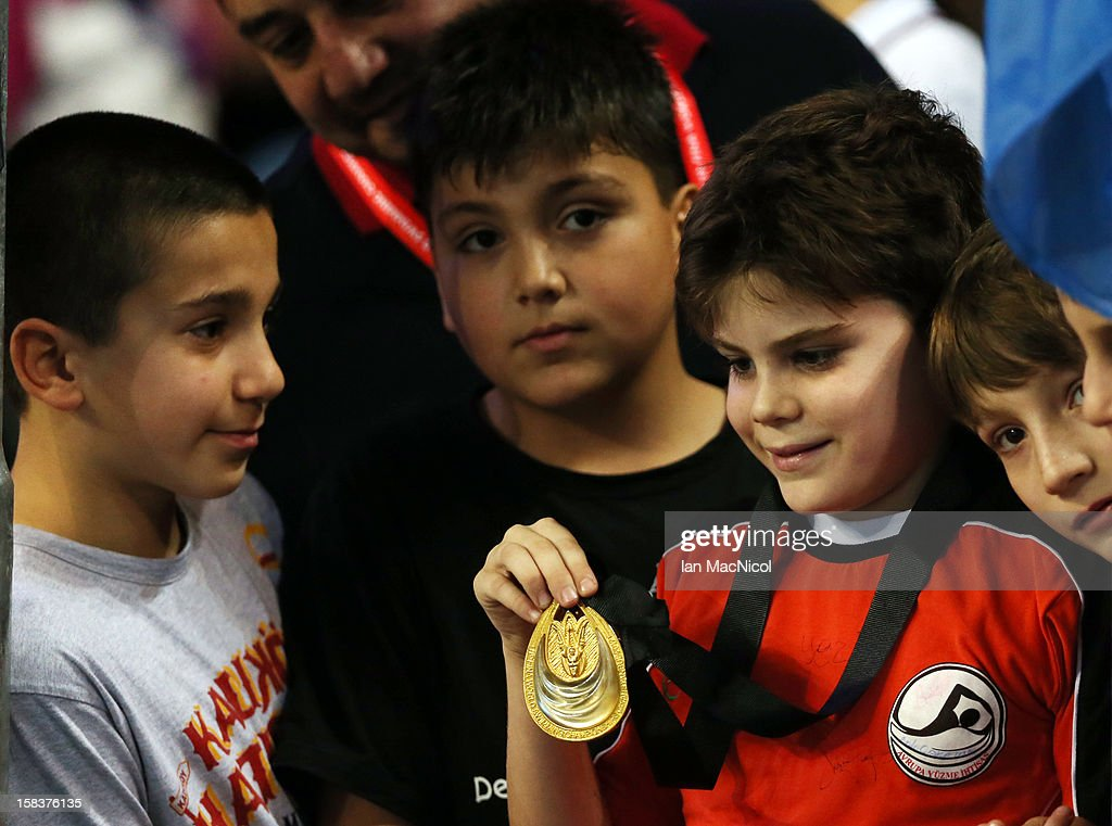 A young boy shows off the gold medal Ryan Lochte of USA gave him from his victory in the Men's 200m IM final during day three of the FINA World Short Course Swimming Championships on December 14, 2012 in Istanbul, Turkey.