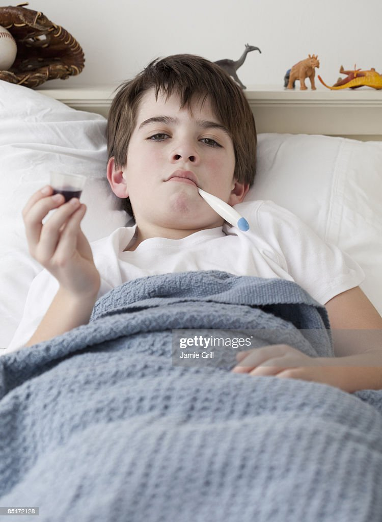 Young Boy Sick in Bed with Medicine : Stock Photo