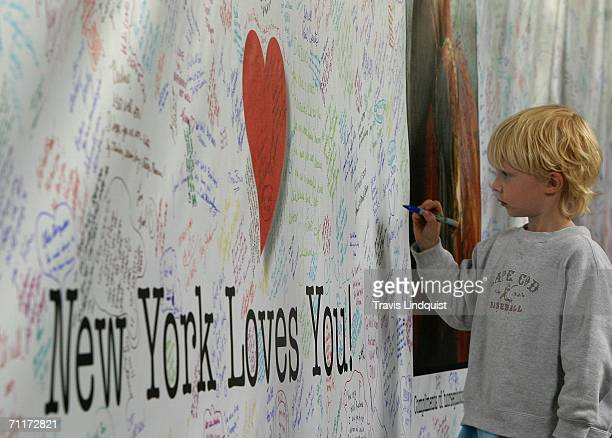 A young boy signs a get well card for Barbaro winner of the Kentucky Derby before 138th running of of the Belmont Stakes on June 10 2006 at Belmont...