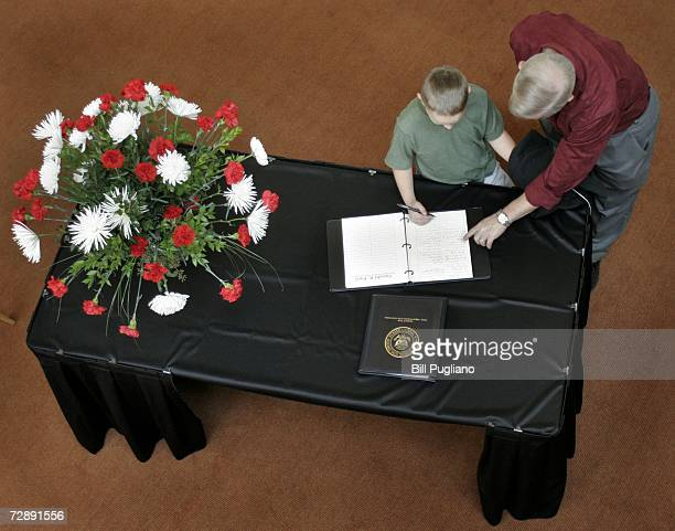 A young boy signs his name in a condolence book at the Gerald R Ford Presidential Library December 28 2006 in Ann Arbor Michigan The former US...