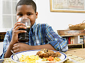 Young Boy Sits at a Table With a Plate of Food, Drinking a Glass of Cola