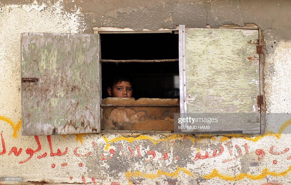 A young boy sits at the window of the home of Haitham Al-Meshal, during his funeral in Gaza City, on April 30, 2013. An Israeli air strike on Gaza City killed one person Palestinian officials said, with Israel saying it targeted a militant involved in a rocket attack on Eilat on April 17.