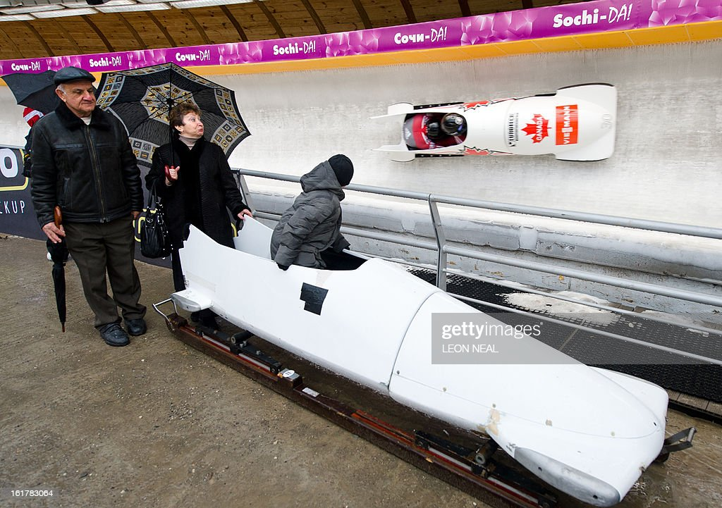 A young boy sits in a bobsleigh during the Men's 2-man Bobsleigh event at the FIBT Bob & Skeleton World Cup at the Sanki Sliding Centre, some 50 km from Russia's Black Sea resort of Sochi, on February 16, 2013. With a year to go until the Sochi 2014 Winter Games, construction work continues as tests events and World Championship competitions are underway.