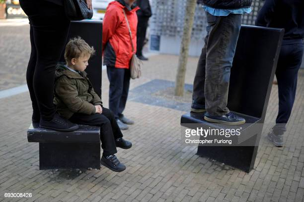 A young boy sits it out as people stand on benches to see Labour Leader Jeremy Corbyn deliver a speech during a rally at Southwater Library on June 6...