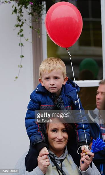 A young boy sits on his mothers shoulders as they watch the bands march past during the 132nd Durham Miners Gala on July 9 2016 in Durham England...