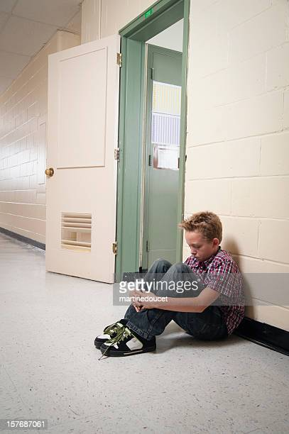 Young boy sitting alone out of classroom.