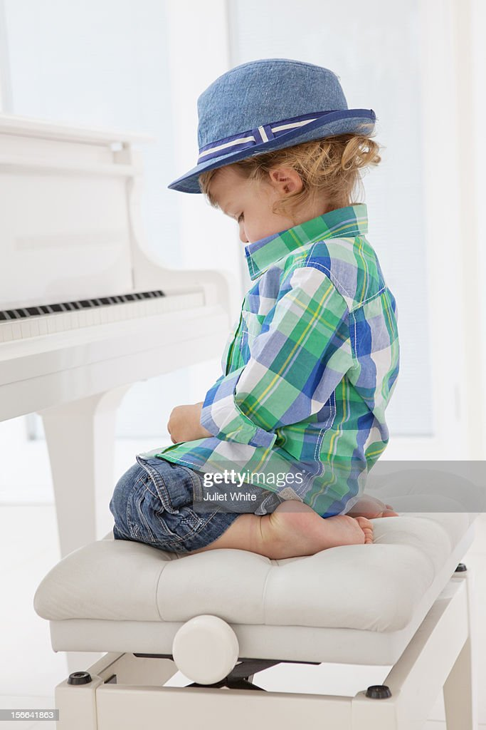Young boy sitting at a piano : Foto de stock