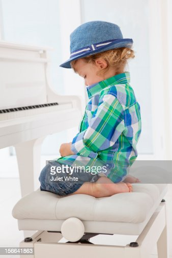Young boy sitting at a piano : ストックフォト