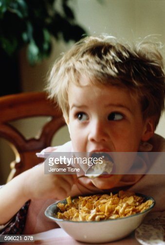 Young boy (5-7) sitting at table, eating breakfast cereal : Stock Photo