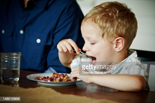 Young boy sitting at table eating fruit crisp : Stock Photo