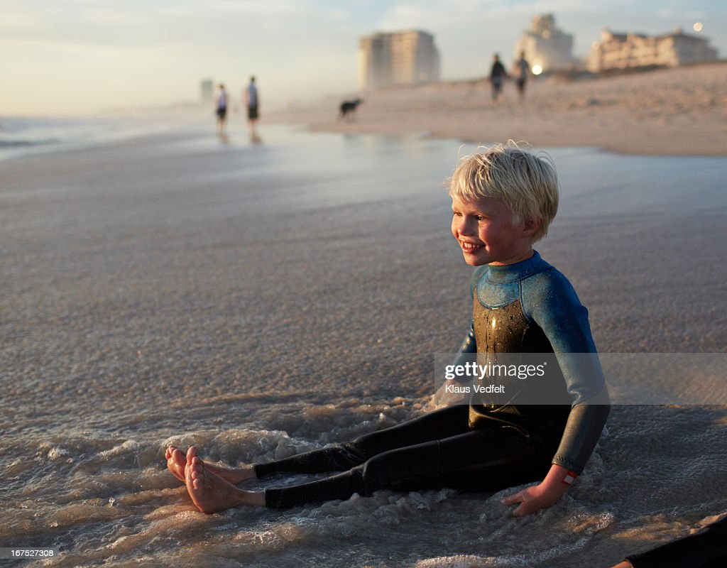 Young boy sitting at water edge on the beach : Stock Photo