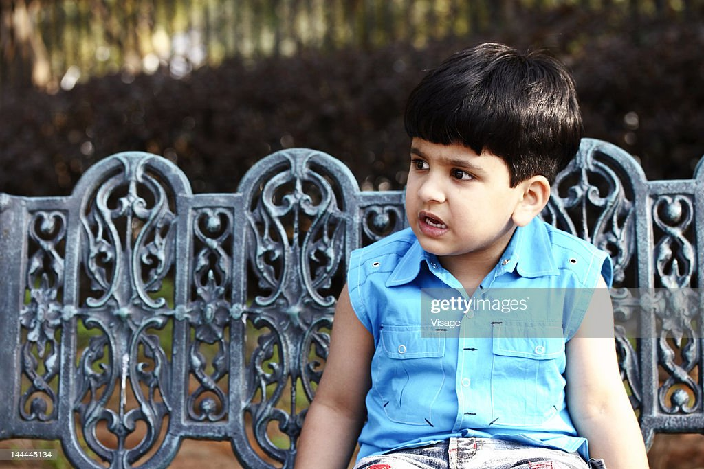 Young boy sitting in a park bench : Stock Photo