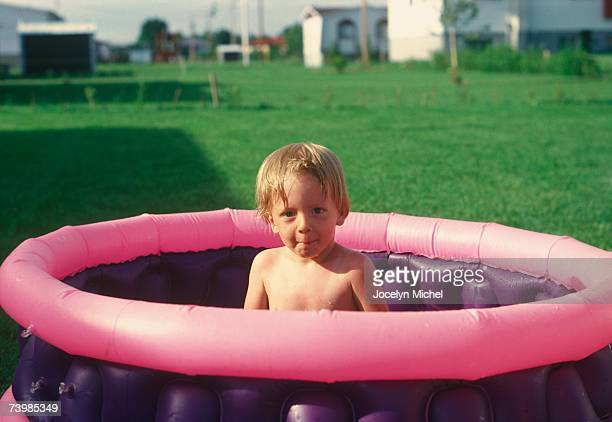 Young boy sitting in a wading pool