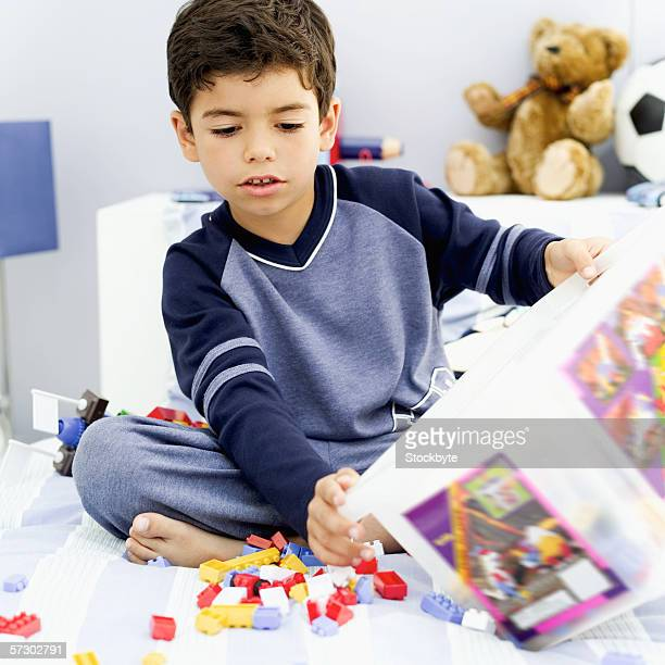 Young boy (8-9) sitting in bed with a box of puzzle pieces