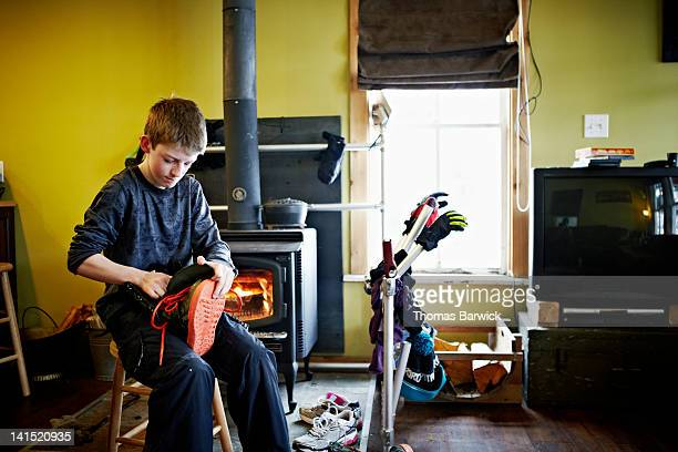 Young boy sitting in cabin by wood stove