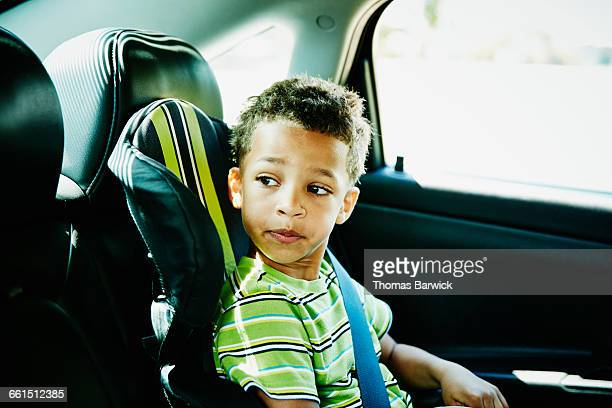 Young boy sitting in car seat looking out window