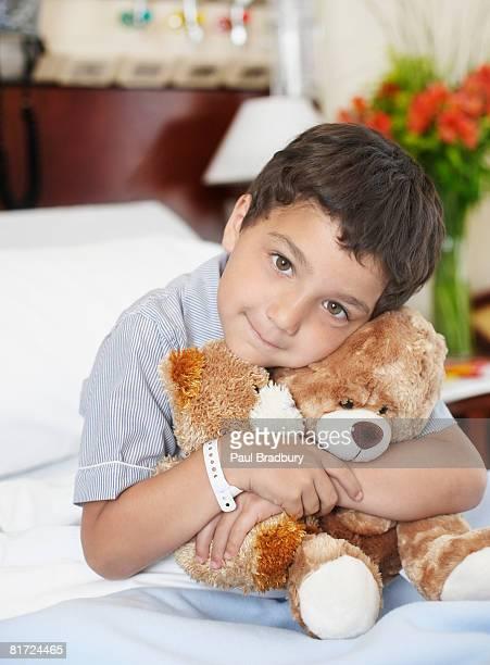 Junge sitzt im Krankenhaus-Bett mit teddy Bären