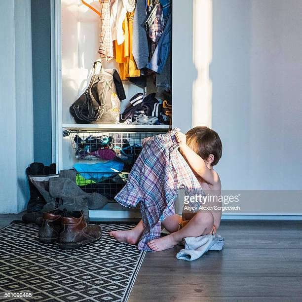 Young boy sitting next to wardrobe, holding shirt