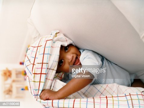 Young Boy Sitting on a Chair and Playing Under a Sheet