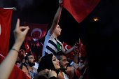 A young boy sitting on a man's shoulders waves a Turkish flag during a meeting in support of the Turkish president on Taksim Square in Istanbul on...