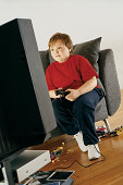 Young Boy Sitting on a Sofa in His Living Room and Playing a Computer Game With a Games Controlller on Tv
