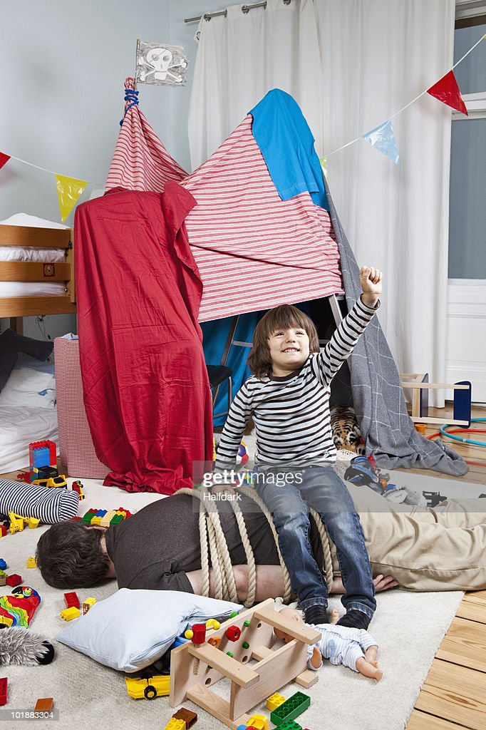 A young boy sitting on a tied up man in a child's playroom : Stock Photo