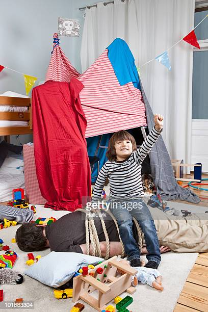 A young boy sitting on a tied up man in a child's playroom