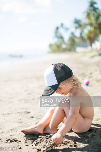 Young boy sitting on beach, digging in sand