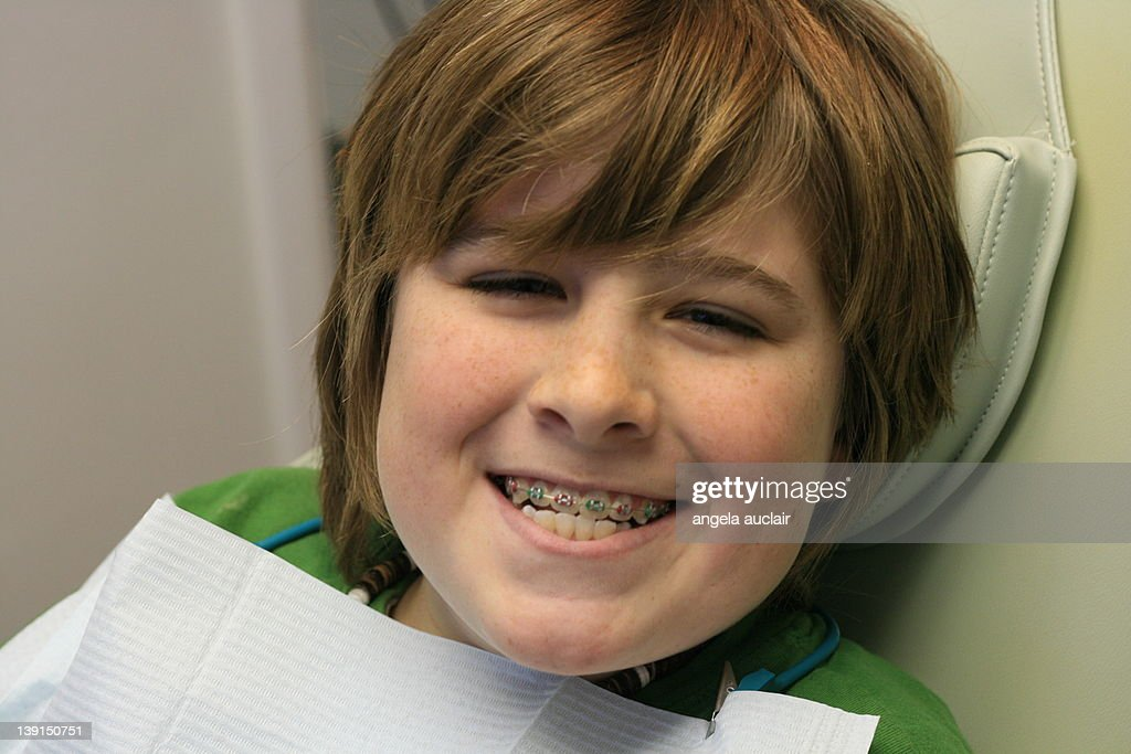 Young boy sitting on dentist chair smiling : Stock Photo