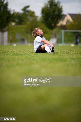 Young boy sitting on football field : Stock Photo