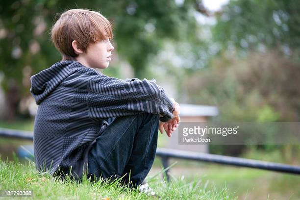 Young Boy Sitting on Hillside