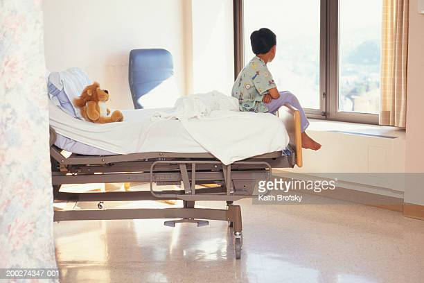 Young boy (6-7) sitting on hospital bed