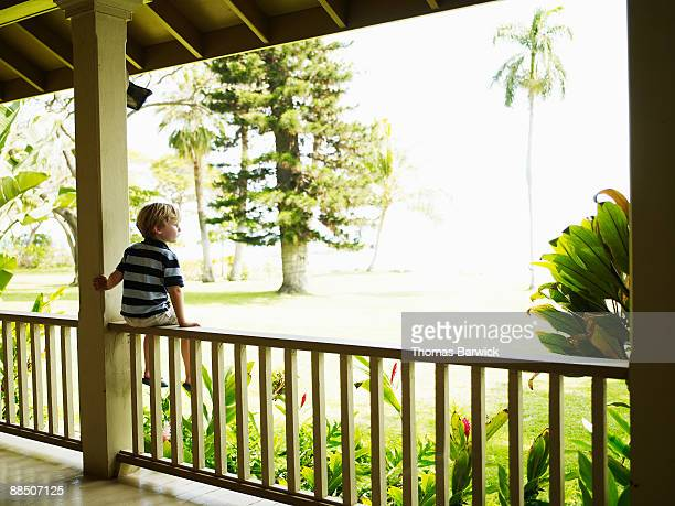 Young boy sitting on porch rail looking out