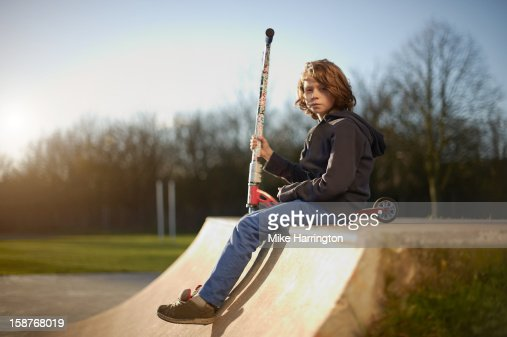 Young boy sitting on ramp at skate park. : Stock Photo