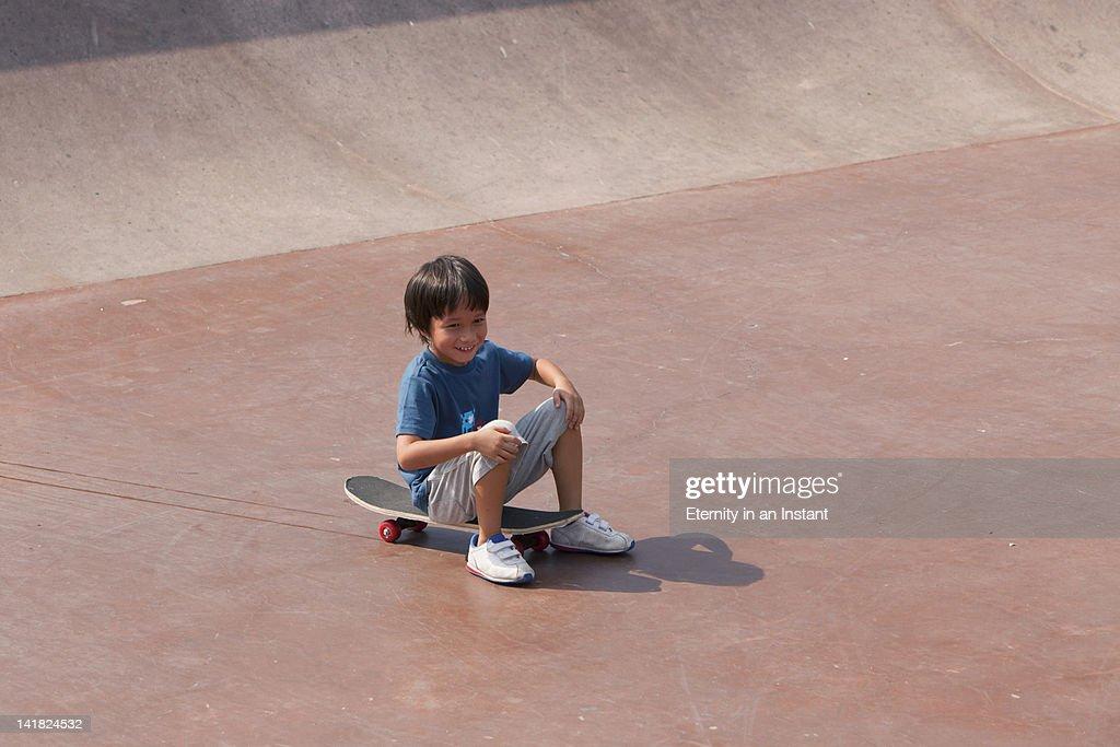 Young boy sitting on skateboard at skateboard park : Stock Photo