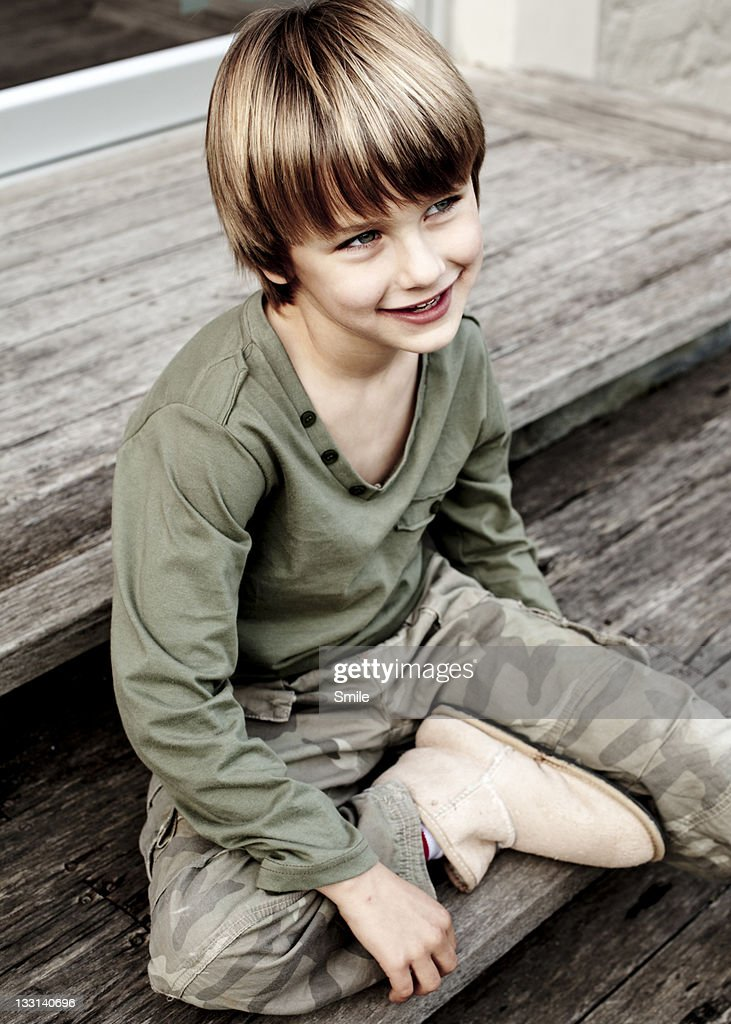 Young boy sitting on step smiling : Stock Photo