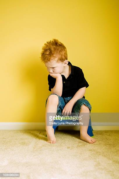 Young boy sitting on stool with chin in hand