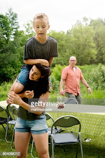 Young boy sitting on teenage girl shoulders outdoors in summer. : Stock Photo