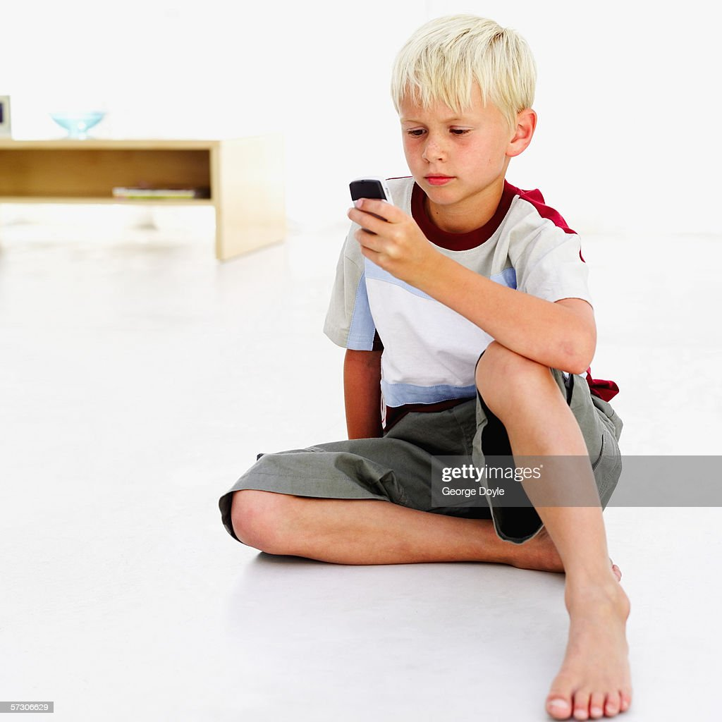 young boy sitting on the floor operating a mobile phone stock photo getty images. Black Bedroom Furniture Sets. Home Design Ideas