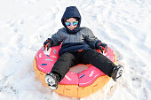 Young boy sledding on a donut innertube in the snow during winter