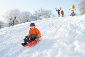 Young Boy Sledging Down Hill With Family Watching And Cheering